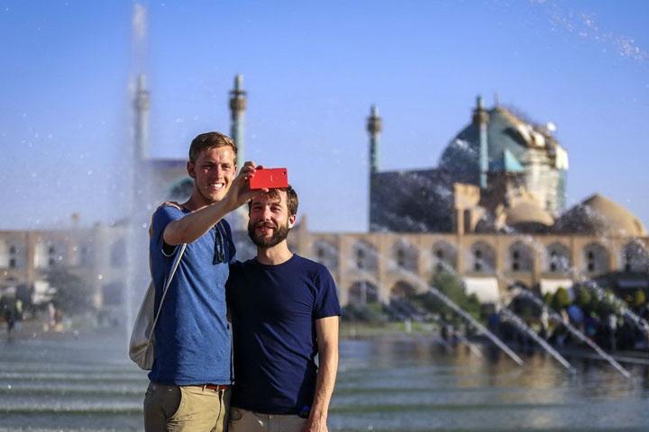 السفر إلى إيران ، والسياح تأخذ صورة شخصية أمام مسجد الإمام في أصفهان